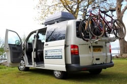 A two berth camper, with bike rack and roof storage box.